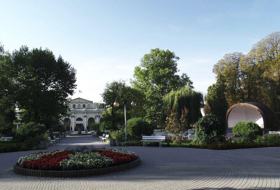 Fotografia prezentująca fragment parku uzdrowiskowego wBusku Zdroju. Na pierwszym planie widoczny okrągły klomb, od którego prowadzi aleja wkierunku budynku zkolumnami.