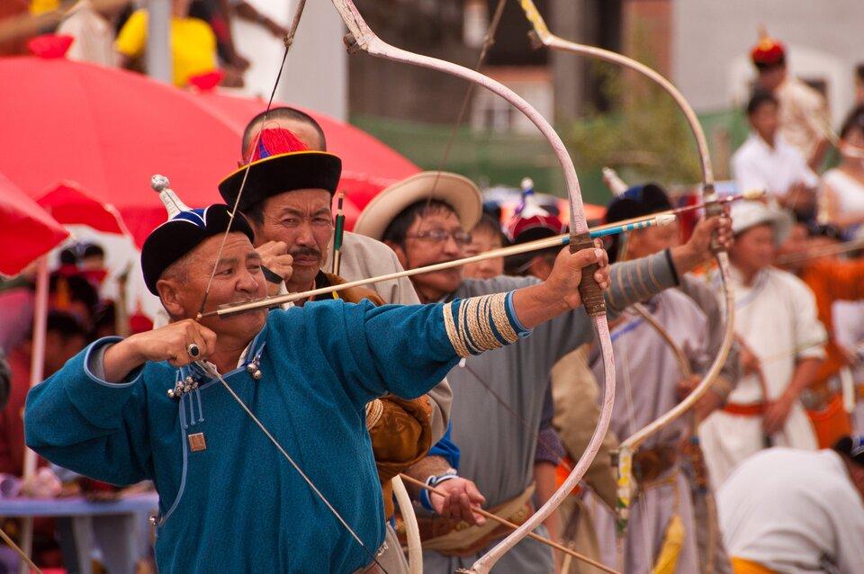 Łucznicy wtradycyjnych mongolskich strojach podczas dorocznego festiwalu sportowego Nadaam wUłan Bator. Wkadrze wyraźnie przedstawieni są trzej zawodnicy na tle pozostałych. Dwóch zwróconych wprawą stronę kadru mierzy zzakrzywionych łuków, atrzeci spogląda wstronę fotografa.