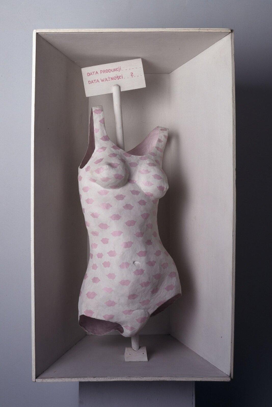 """Ilustracja przedstawiająca asamblaż Marii Pinińskiej-Bereś, """"Czy kobieta jest człowiekiem?"""". Przedstawia on jednoczęściowy kostium kobiecy, biały, na którym znajdują się różowe usta, rozmieszczone równomiernie. Nad kostiumem znajduje się kartka znapisami: """"DATA PRODUKCJI. DATA WAŻNOŚCI?""""."""