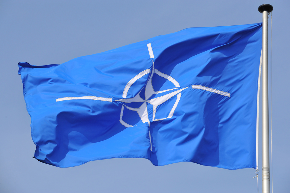 Zdjęcie przedstawia flagę NATO zawieszoną na maszcie. Maszt po prawej stronie. Flaga unosi się ijest skierowana wlewo. Na błękitnym tle znajduje się biały pierścień. Wśrodku pierścienia czteroramienna gwiazda. To tak zwana róża kompasowa. Ramiona gwiazdy są zakończone białym, wąskim paskiem.