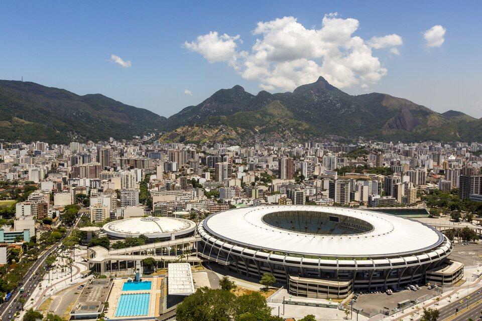 Na zdjęciu miasto ustóp gór, nowoczesne wysokie budynki, na pierwszym planie kompleks zabudowań sportowych zokrągłym stadionem ibasenami.