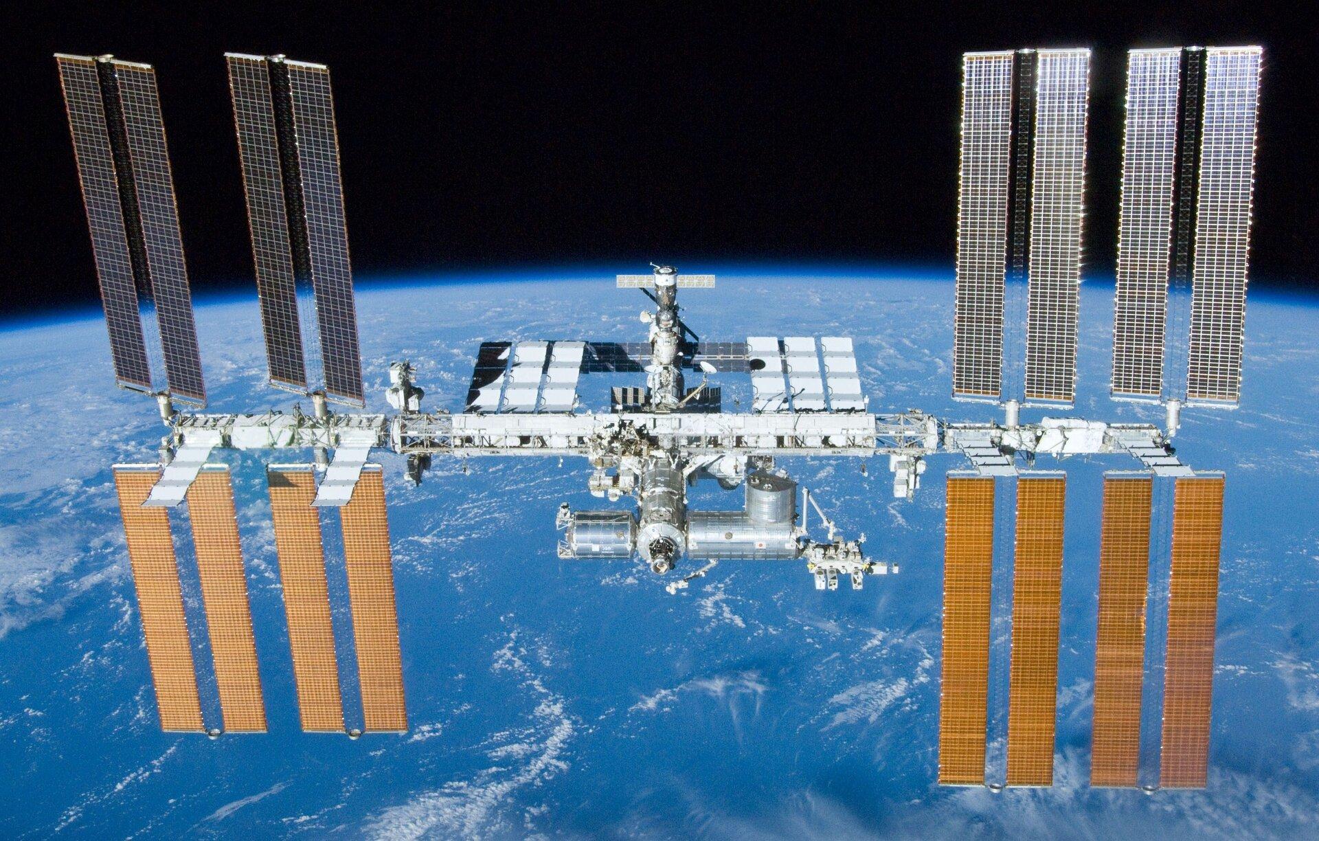 Zdjęcie przedstawia międzynarodową stację kosmiczną ISS na tle kuli ziemskiej.