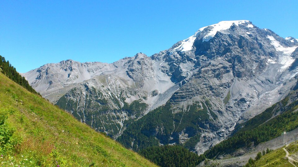 Na zdjęciu skalisty szczyt górski pokryty śniegiem. Wdolnej części porośnięty lasem iglastym.