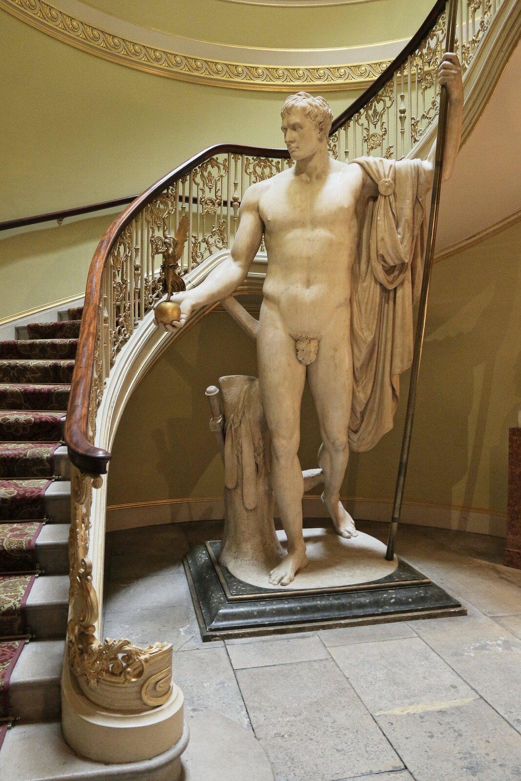 """Ilustracja przedstawia dzieło Antonio Canova """"Napoleon jako Mars"""". Ukazuje Napoleona jako monumentalnego, stylizowanego na greckiego boga Marsa. Jest to akt wpostawie kontrapostu. Napoleon wprawej dłoni trzyma jabłko zpozłacaną boginią Nike. Na lewym ramieniu przerzucony ma płaszcz, awdłoni trzyma włócznie."""