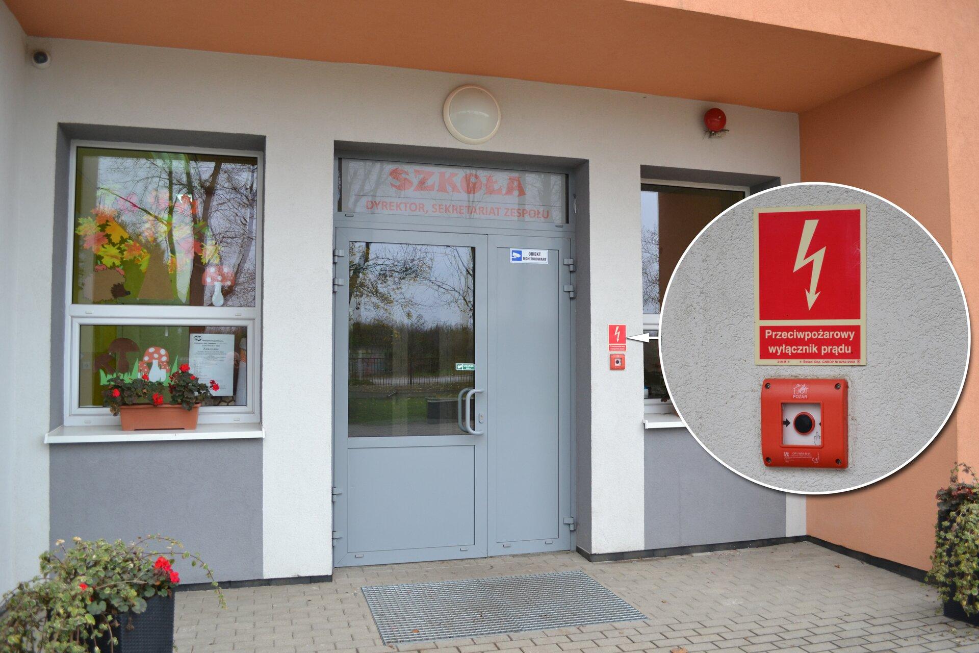 Kolorowe ujęcie głównego wejścia do budynku szkoły za dnia. Wejście to duże przeszklone pojedyncze drzwi zczerwonym napisem szkoła powyżej. Zprawej strony drzwi mieście się przeciwpożarowy wyłącznik prądu, który sygnalizuje czerwona ramka. Powyżej czerwona prostokątna tabliczka. Tabliczka podzielona na dwie części. Górna część, zajmująca dwie trzecie tabliczki, to czerwony prostokąt. Przez środek prostokąta przebiega biała błyskawica wkształcie strzałki zgrotem skierowanym ku dołowi. Wpołowie strzałka jest zakrzywiona wformie zygzaka. Dół tabliczki to biały napis: główny wyłącznik prądu.