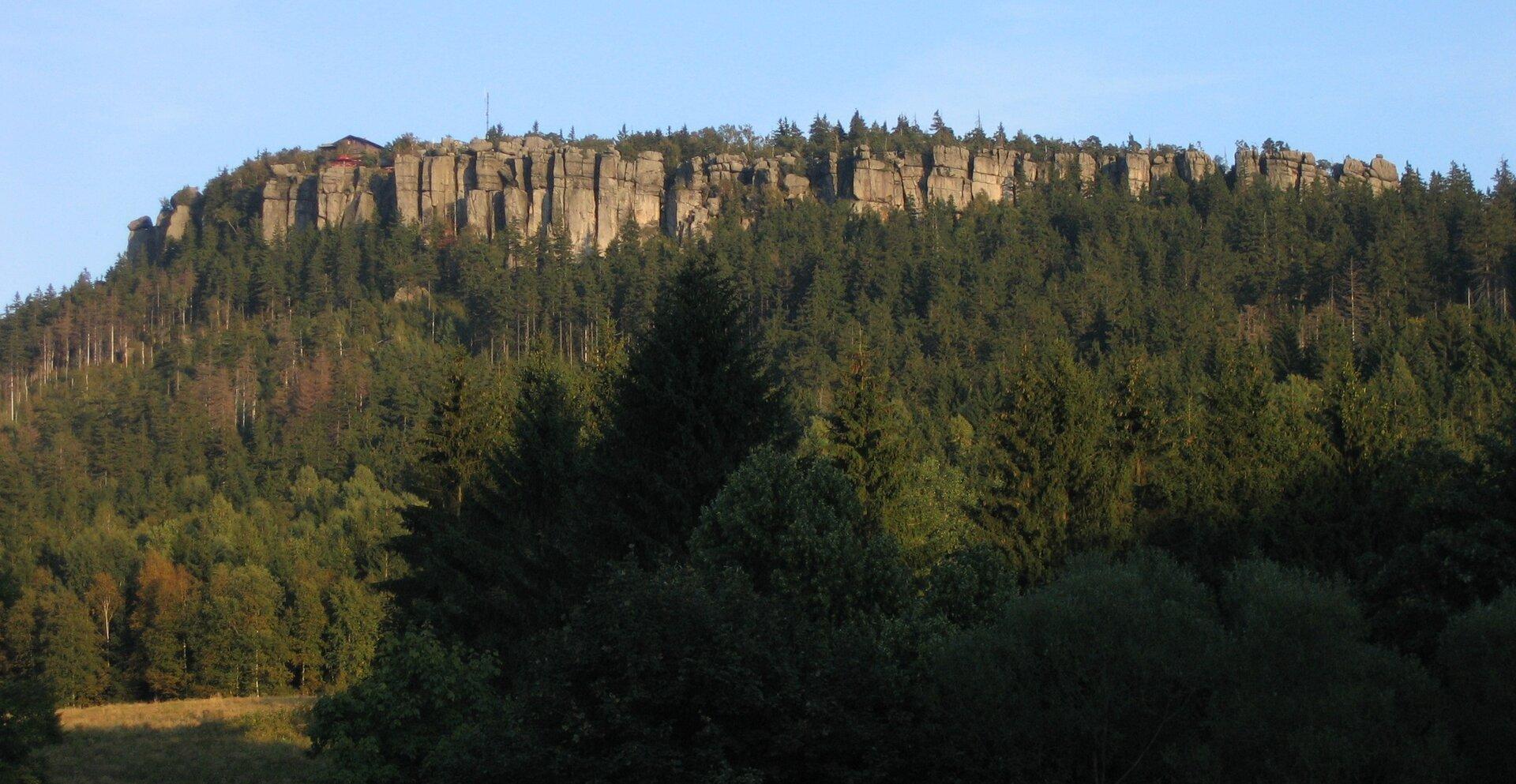 Na zdjęciu trapezoidalny blok skalny porośnięty lasem iglastym. Powierzchnia szczytu jest zwietrzała ipopękana.