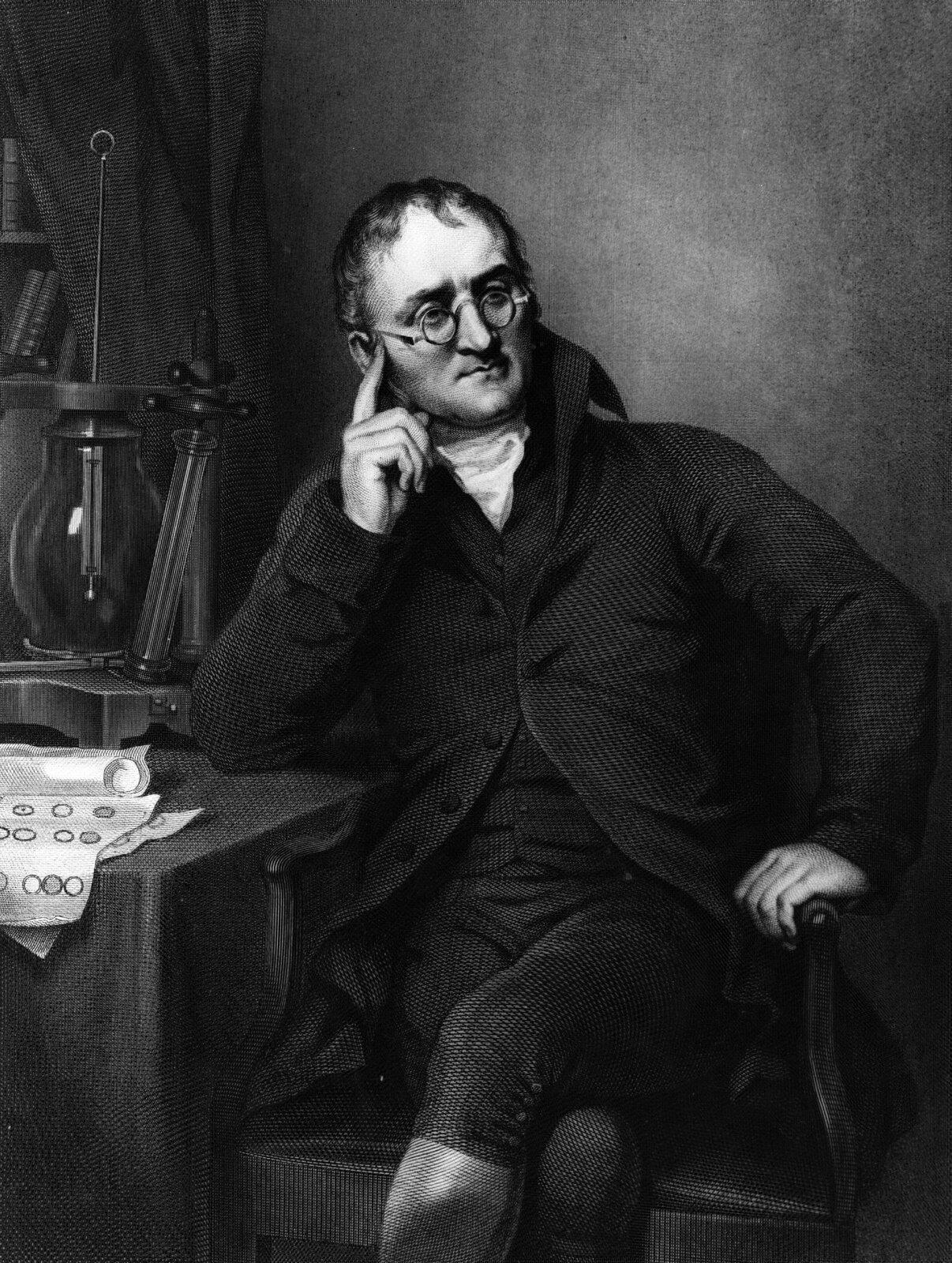 Zdjęcie przedstawia portret Johna Daltona. Portret czarno biały. Mężczyzna wwieku około pięćdziesięciu pięciu lat. Mężczyzna siedzi na krześle wsparty prawym łokciem oblat biurka. Prawa dłoń sięga do twarzy mężczyzny. Palec wskazujący skierowany jest wstronę skroni. Lewa ręka spoczywa na podłokietniku krzesła. Głowa mężczyzny skierowana wprawą stronę. Czoło wysokie miejscami przykryte kępami włosów. Czarne włosy zaczesane do tyłu. Nos duży, wyrazisty. Okulary wokrągłych oprawach. Usta wąskie. Broda bardzo ostro zakończona. Nogi założone jedna na drugą. Mężczyzna ubrany wbiałą koszulę iciemny garnitur. Buty wysokie sięgające kolan