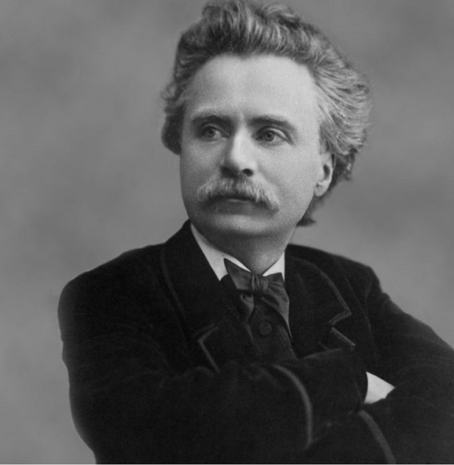 Ilustracja przedstawia fotografię Edvarda Griega. Mężczyzna ukazany jest zprawego półprofilu, od pasa wgórę. Postać ubrana jest wczarny płaszcz oraz jasną koszulę zprzeplecioną pod szyją muszką.