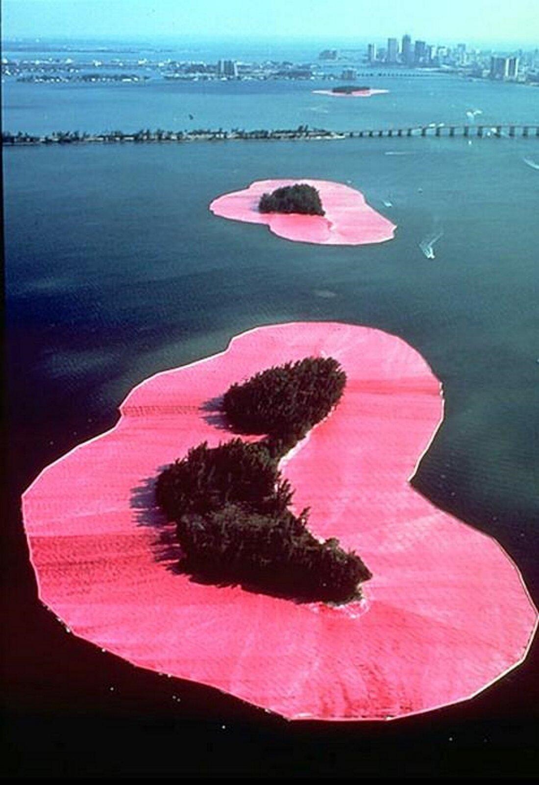 """Ilustracja przedstawia obraz Christo Jawaszew iJeanne-Claude pt. """"Surrounded Islands"""" (""""Otoczone wyspy""""). Obraz powstał w1983 roku. Autorzy dzieła byli małżeństwem, które tworzyło dzieła sztuki związane zochroną środowiska. Na obrazie przedstawiony jest duży zbiornik wodny. Wjego centralnym punkcie znajduje się różowa wyspa zkrzewami pośrodku. Woddali znajduje się podobna, mniejsza wyspa. Wtle widoczne są zabudowania oraz fragment miasta."""