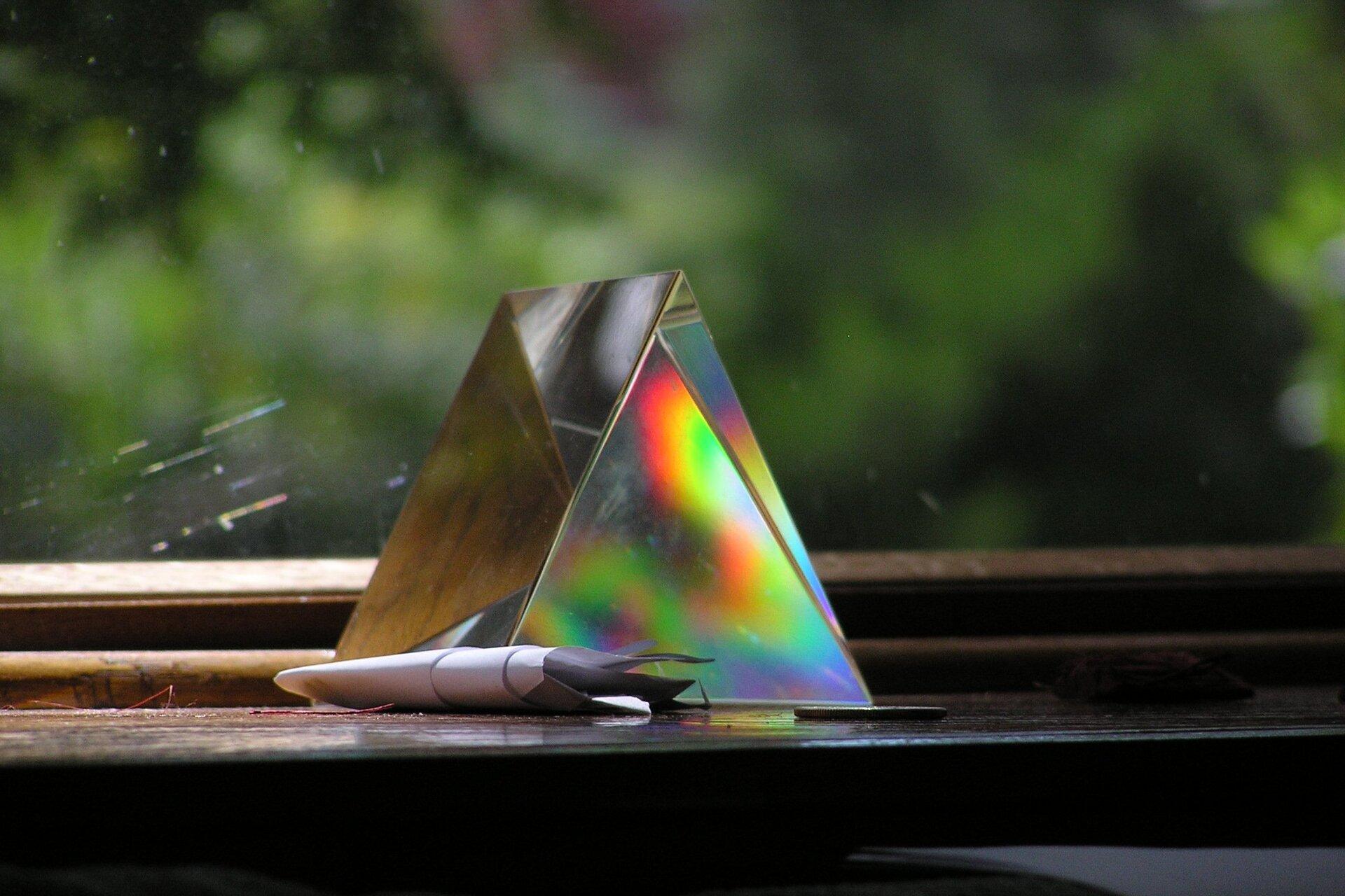 Zdjęcie przedstawia trójkątny pryzmat szklany stojący na parapecie okiennym ioświetlany przez rozproszone światło słoneczne padające zlewej strony. Przez przednią ściankę pryzmatu można zaobserwować, jak na jednej ze ścianek przeciwległych tworzą się różnobarwne plamy, efekt rozszczepienia światła. Wtle szyba okienna za którą wobszarze nieostrości zdjęcia znajduje się zielona roślinność.