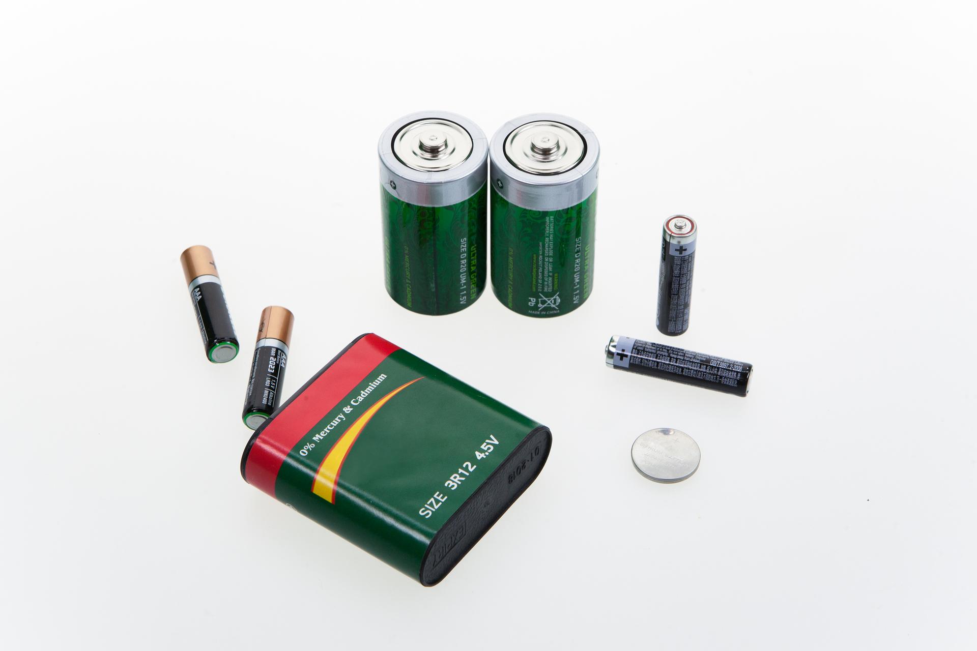 Zdjęcie przedstawia różnego rodzaju baterie na białym tle. Widać tu klasyczne paluszki, czyli baterie AA iAAA, większe baterie R20 ibaterię płaską starego typu, atakże baterię typu mini do kalkulatorów iinnych małych urządzeń.