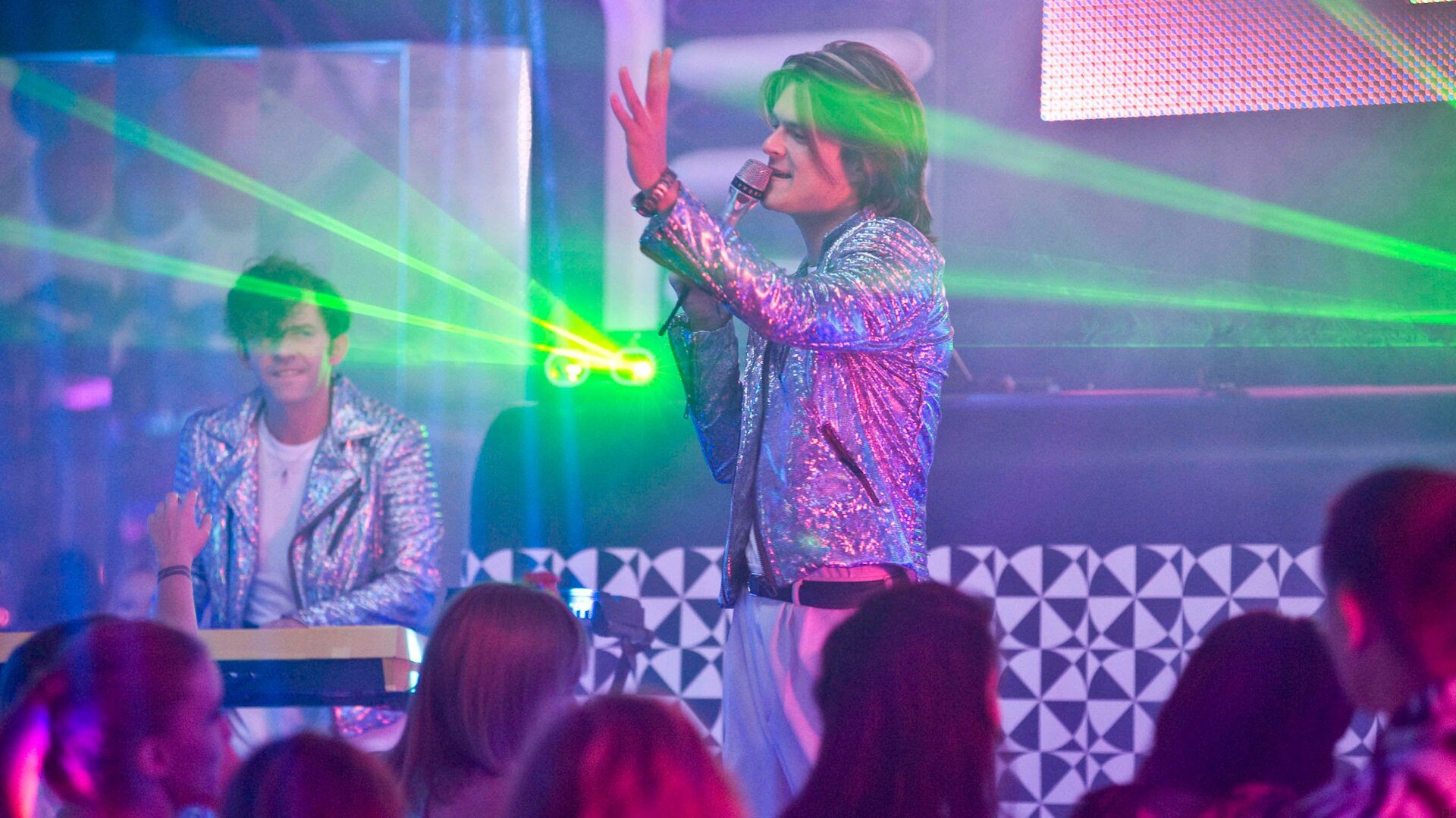 Ilustracja przedstawia koncert muzyki disco. Na pierwszym planie mężczyzna zmikrofonem. Piosenkarz ma dłuższe, sięgające za ucho włosy. Ubrany jest wjasne spodnie ibardzo błyszczącą, krótką kurtkę. Wtle mężczyzna grający na instrumentach klawiszowych. Ze sceny widać laserowe wiązki światła. Przed sceną grupka młodzieży.