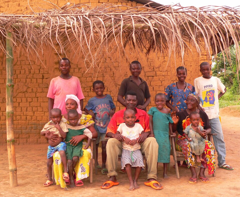 Na zdjęciu kilkunastoosobowa rodzina przed domem pod daszkiem zliści. Kolorowe ubrania. Dużo dzieci.