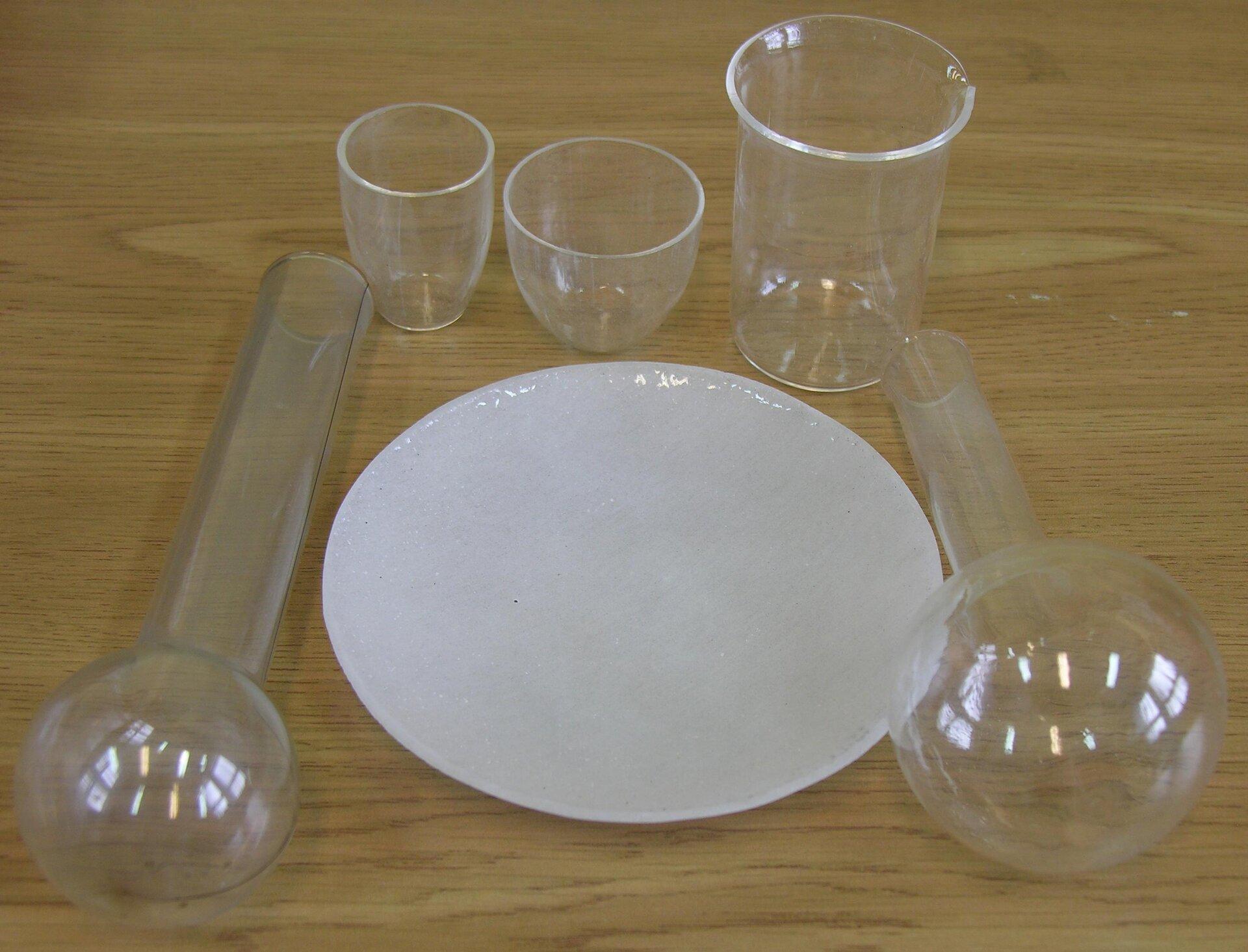 Fotografia przedstawia zestaw do doświadczeń chemicznych. Są to szklane naczynia laboratoryjne oróżnych kształtach, niezbędne do pracy zsubstancjami wpracowni przyrodniczej.
