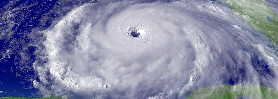 Kolorowe zdjęcie zkosmosu pokazujące formowanie się cyklonu. Na fotografii przedstawiony został fragment kuli ziemskiej otoczony chmurami. Wcentralnej części zdjęcia chmury układają się koliście.
