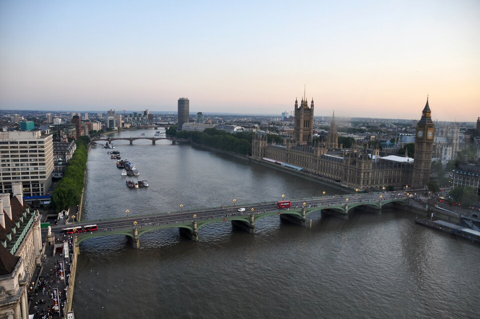 Na zdjęciu szeroka rzeka wobszarze zabudowanym. Zabytkowa inowoczesna zabudowa Londynu, most.