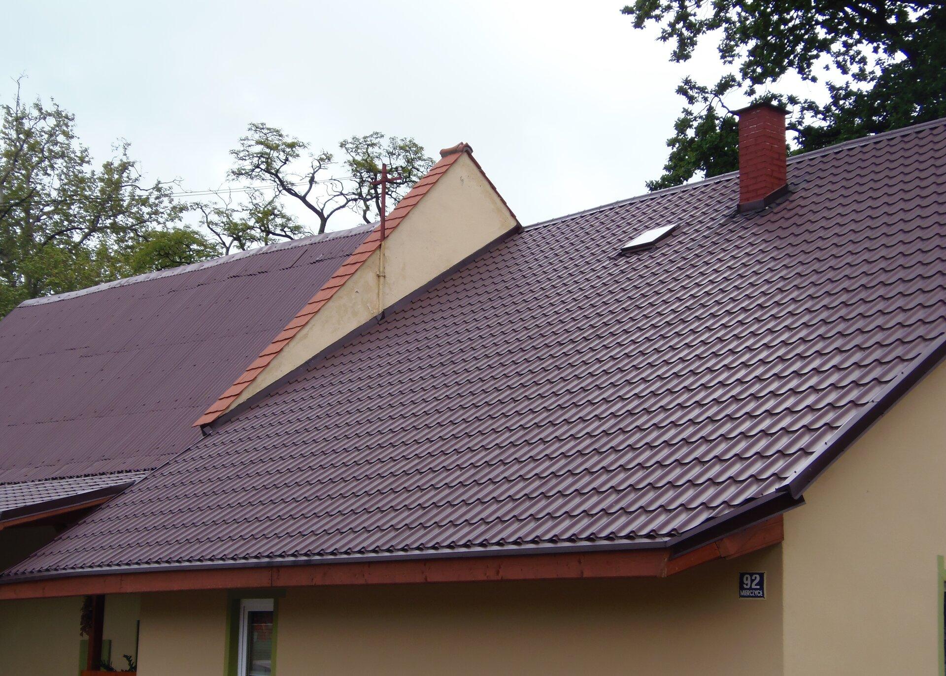 Zdjęcie przedstawia budynek mieszkalny. Cały kadr wypełnia brązowy spadzisty dach wykonany zblachodachówki. Dach podzielony jest na dwie części, gdyż sam budynek składa się zdwóch części przylegających do siebie. Pomiędzy dachem po lewej idachem po prawej stronie znajduje się wymurowana ściana wystająca na około osiemdziesiąt centymetrów nad prawym dachem. Szerokość tego tak zwanego ogniomuru to około czterdzieści centymetrów, ajego szczyt pokryty jest dachówką ceramiczną wkolorze czerwonym.