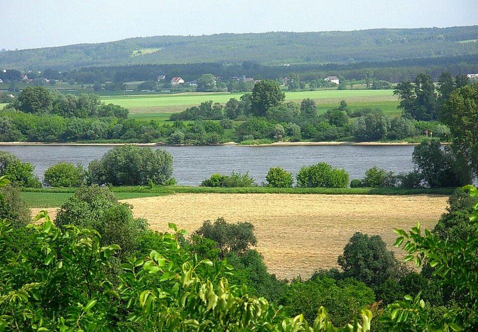 Na zdjęciu rzeka wszerokiej dolinie wpłaskim terenie. Wtle zalesione wzniesienia.