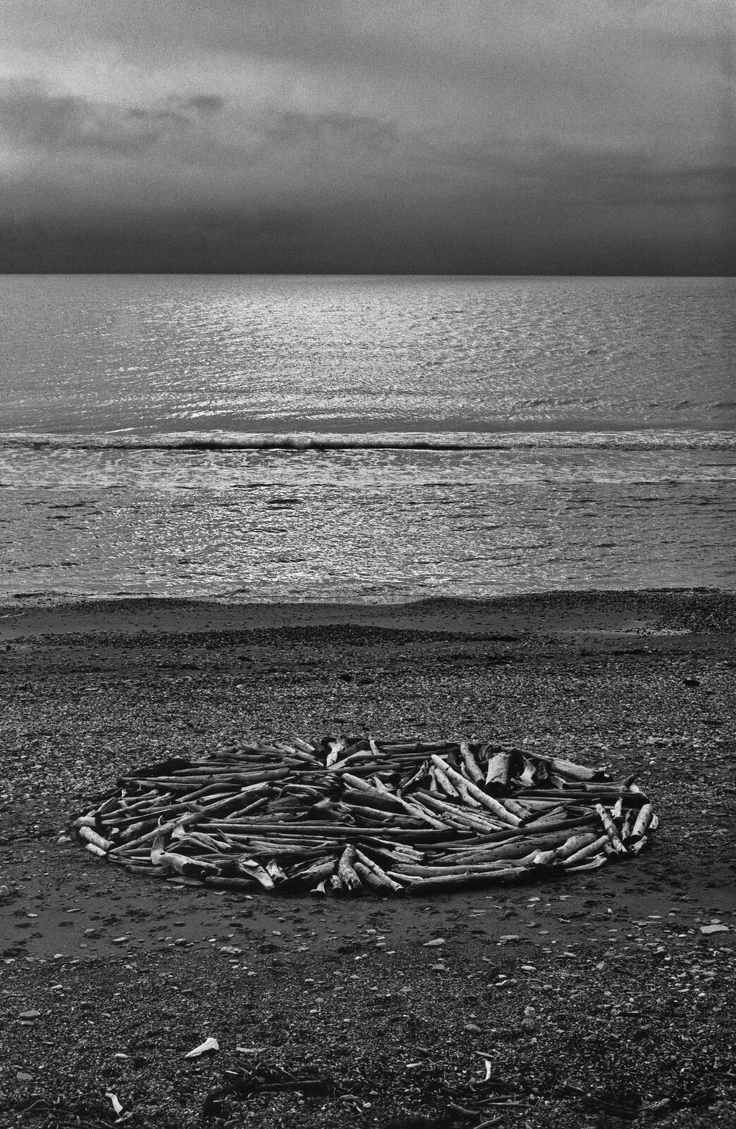 Ilustracja przedstawia okrąg zbudowany zkamieni ipatyków. Artysta budował koła zkamieni ipatyków zebranych wczasie podróży po świecie, które następnie dokumentował przy pomocy fotografii, map iopisów.