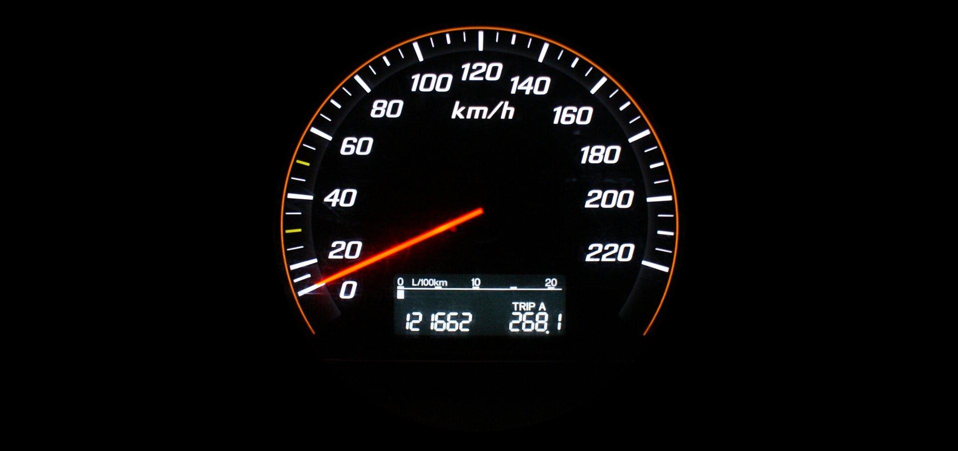 """Zdjęcie przedstawia tarczę prędkościomierza wsamochodzie. Tło itarcza czarne. Tarcza okrągła. Liczby ilitery podświetlane. Skala od 0 do 220, co 20, również podświetlana. Ugóry tarczy, po środku widać litery """"km/h"""". Czerwona wskazówka spoczywa na liczbie 0. Na samym dole cyfrowy wyświetlacz Na nim liczby 12 1662 oraz 268,1."""
