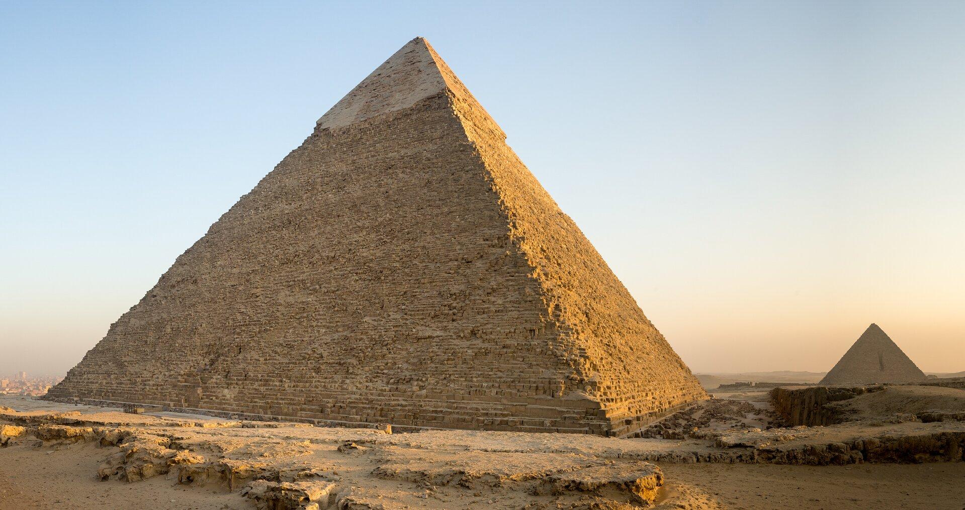 Ilustracja przedstawia piramidę Chefrena wGizie. Piramida ma kształt ostrosłupa opodstawie kwadratu. Jest wkolorze ciemnego piasku. Wtle po prawej stronie widać kolejną piramidę ijasno niebieskie niebo.