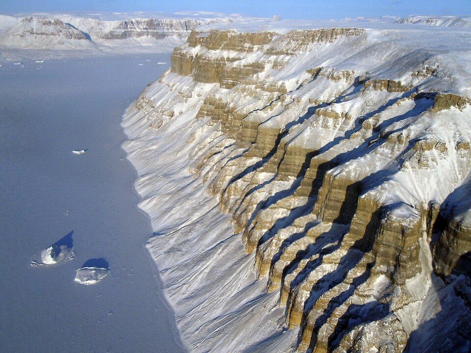 Na zdjęciu bardzo strome skaliste wybrzeże pokryte śniegiem, wdole zamarznięte morze.