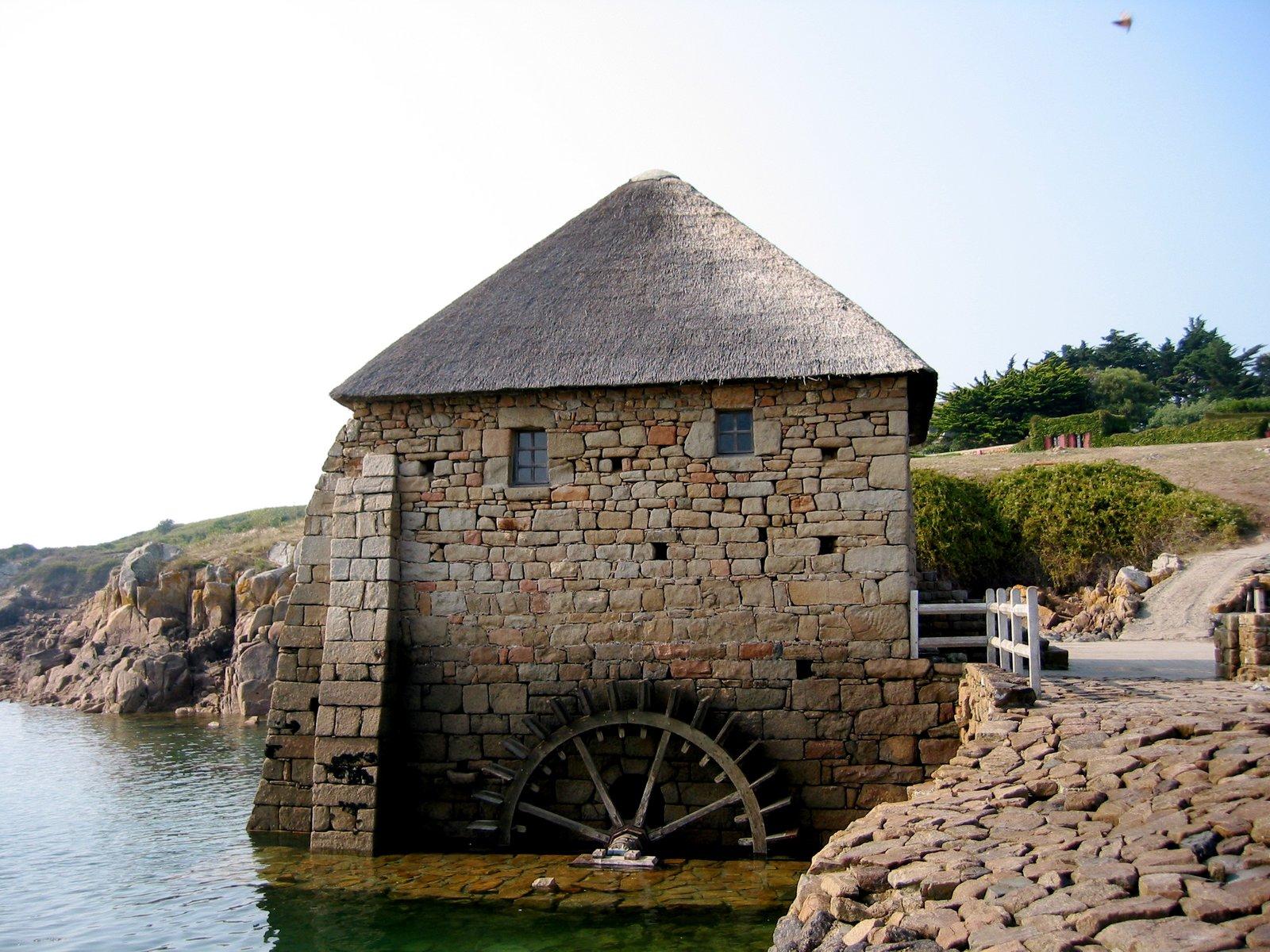 Na zewnętrznej ścianie budynku stojącego przy strumieniu zamontowane jest drewniane koło, które kręci się napędzane płynącą wodą. Pod dachem budynku są dwa małe okna. Wtle jest droga izielone zarośla.