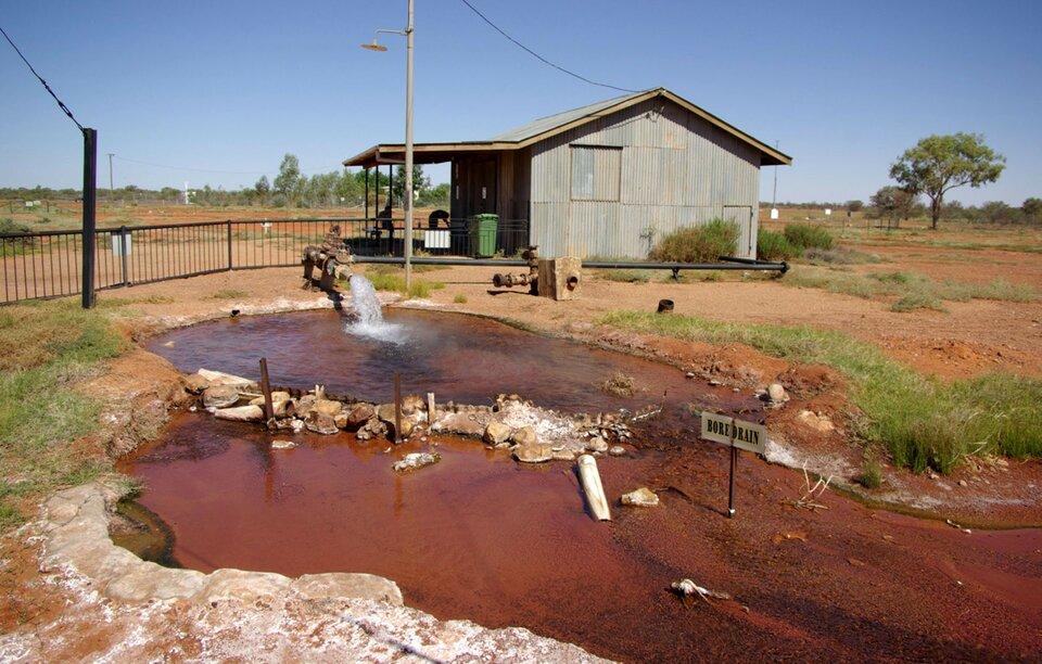 Na zdjęciu niewielki, płytki zbiornik wodny, dno oczerwonawym zabarwieniu. Na brzegu pompa, strumień wody. Wtle zabudowania gospodarskie.