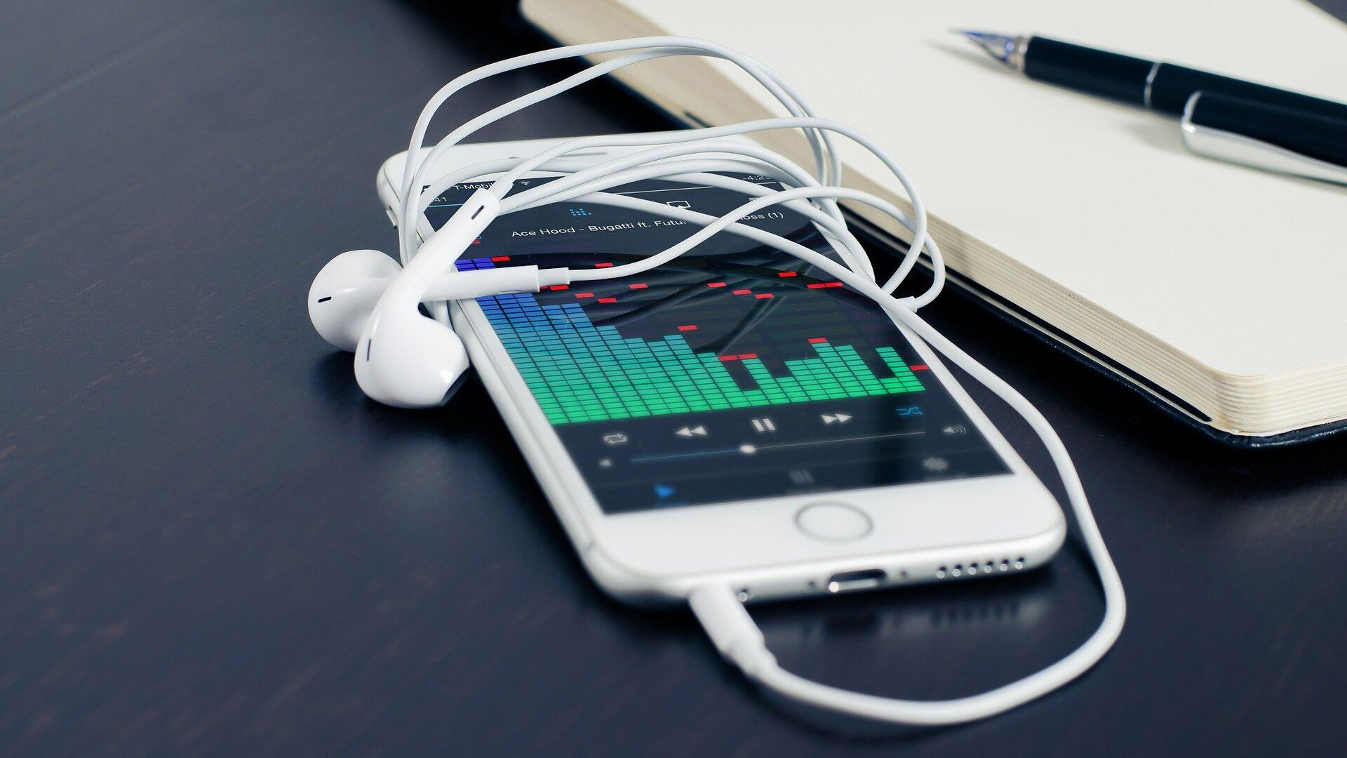 """Zdjęcie przedstawia leżący na niebieskiej gładkiej powierzchni włączony biały smartfon zpodłączonymi białymi słuchawkami. Na ekranie smartfona widać graficzne zobrazowanie odtwarzanego pliku dźwiękowego, co można uznać za przykład graficznego symbolu technologicznego. Poniżej są przedstawione klawisze odtwarzacza: """"przewiń do tyłu"""", """"pauza"""", """"przewiń do przodu"""". Wprawym górnym rogu zdjęcia widoczny jest fragment notesu zleżącym na nim długopisem."""