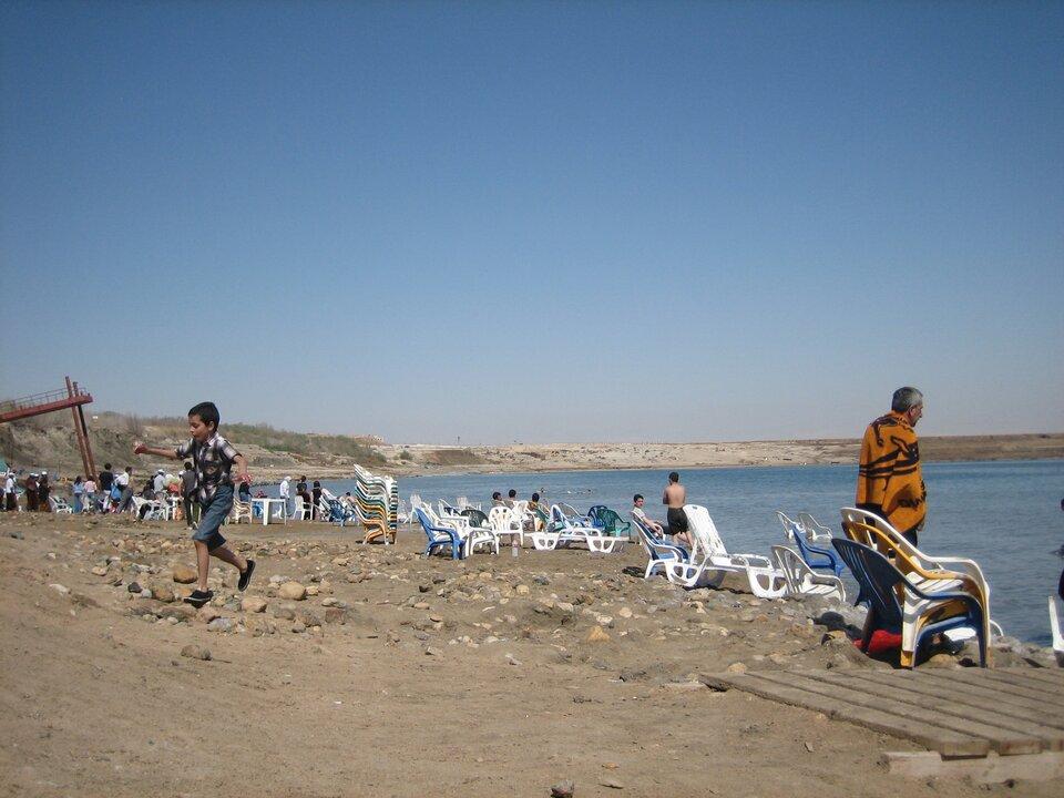 Brzeg morski, piaszczysta plaża zkamieniami, leżaki ikrzesła plażowe.