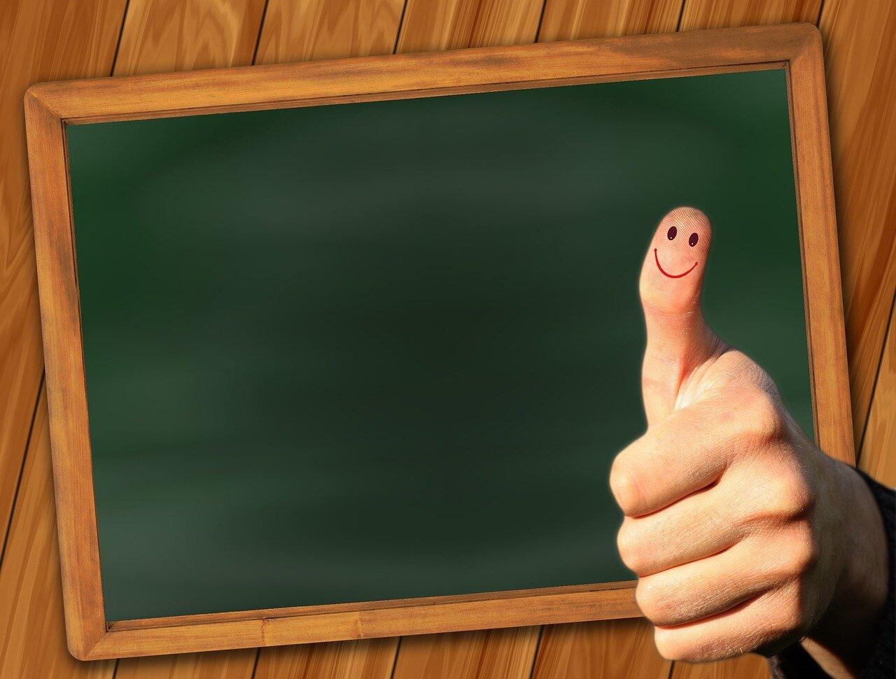 grafika przedstawia tablice na tle które widac kciuk, na kciuku rysunek układajacy sie wuśmiechnięte twarz