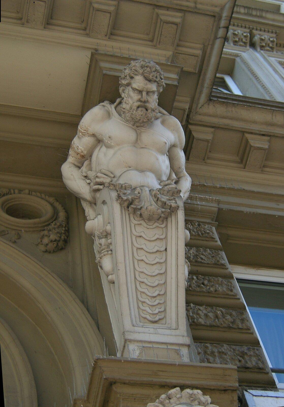 Ilustracja przedstawia ornament – atlant. Element dekoracyjny przymocowany jest do części portalu iprzedstawia on umięśnionego mężczyznę zbrodą. Prawdopodobnie jest to mitologiczny Bóg.