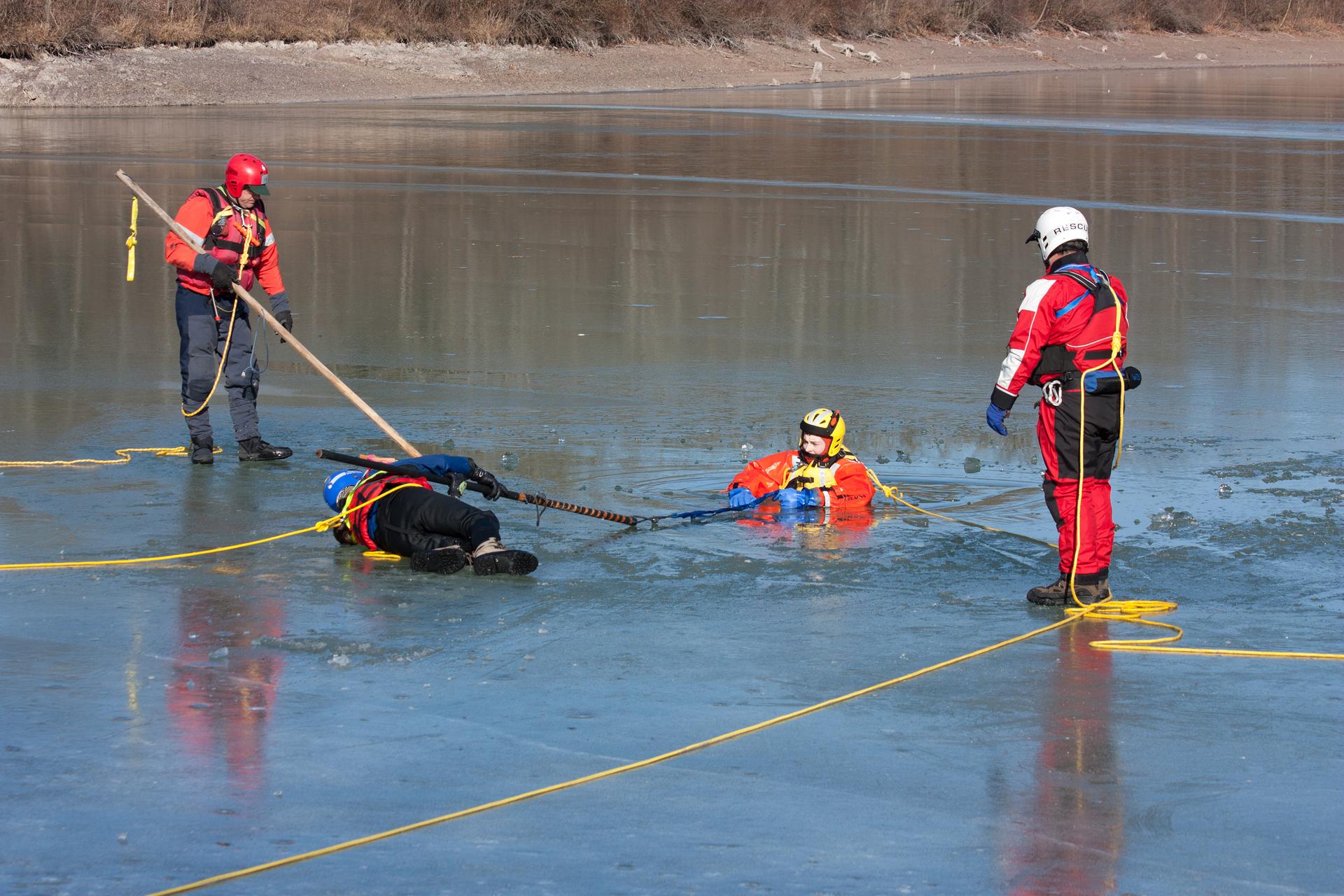 Kolorowe zdjęcie przedstawia ćwiczenia ratowników wodnych. Zimowy słoneczny dzień. Ratownicy ćwiczą wydobywanie tonącego na zamarzniętej powierzchni jeziora. Na środku jeziora przygotowany przerębel. Wprzeręblu tonąca osoba. Dwaj ratownicy stoją po obu stronach przerębla. Jedne po lewej ijeden po prawej. Obydwaj ratownicy przewiązani żółtymi linami. Trzeci ratownik leży na zamarzniętej powierzchni jeziora. Leżący ratownik trzyma długi kij. Drugi koniec kija przytrzymuje osoba tonąca wprzeręblu. Wszyscy ratownicy ubrani są wspecjalne ocieplane kombinezony. Mają kaski na głowach.