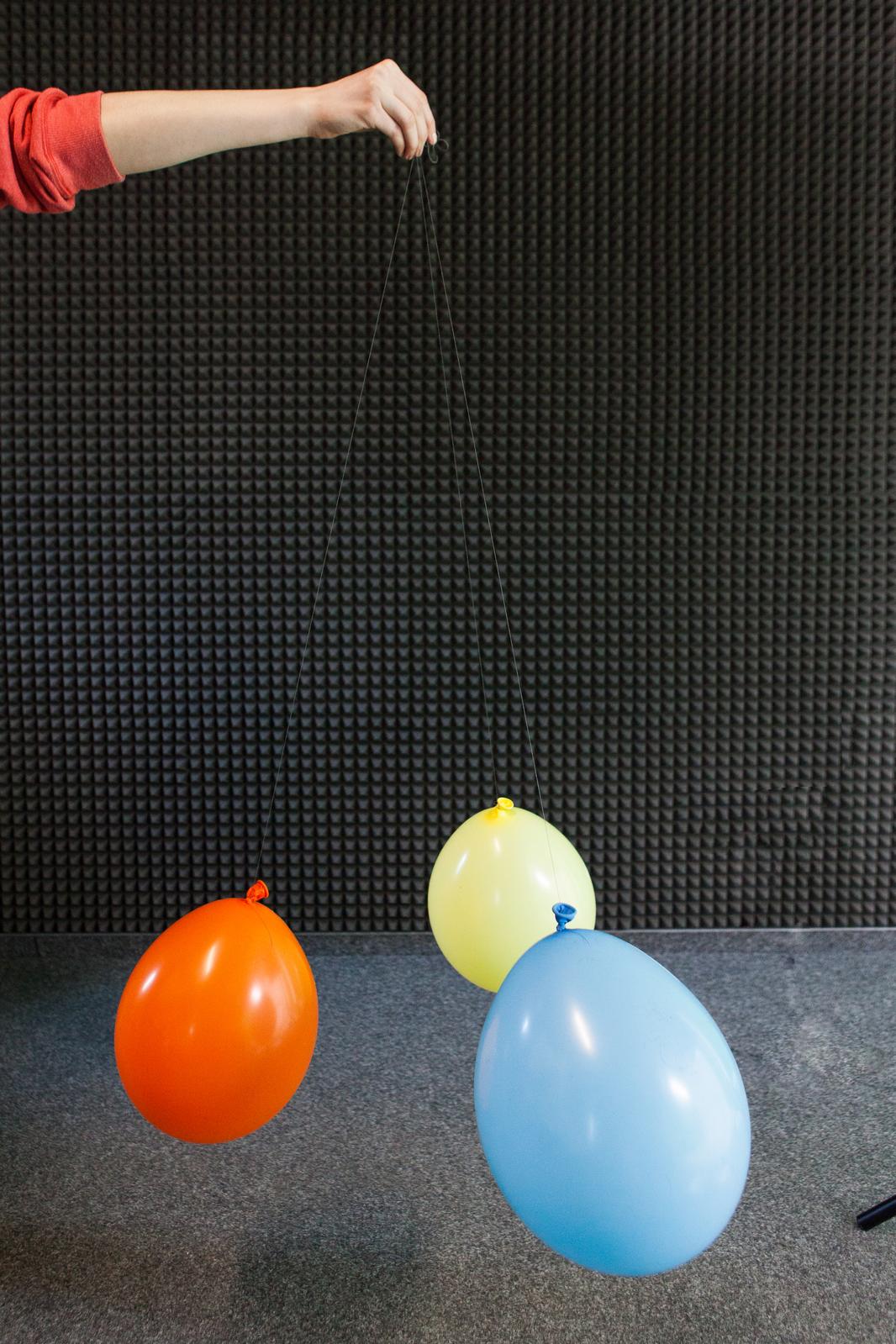 Zdjęcie przedstawiające trzy odpychające się baloniki naelektryzowane jednoimiennie.