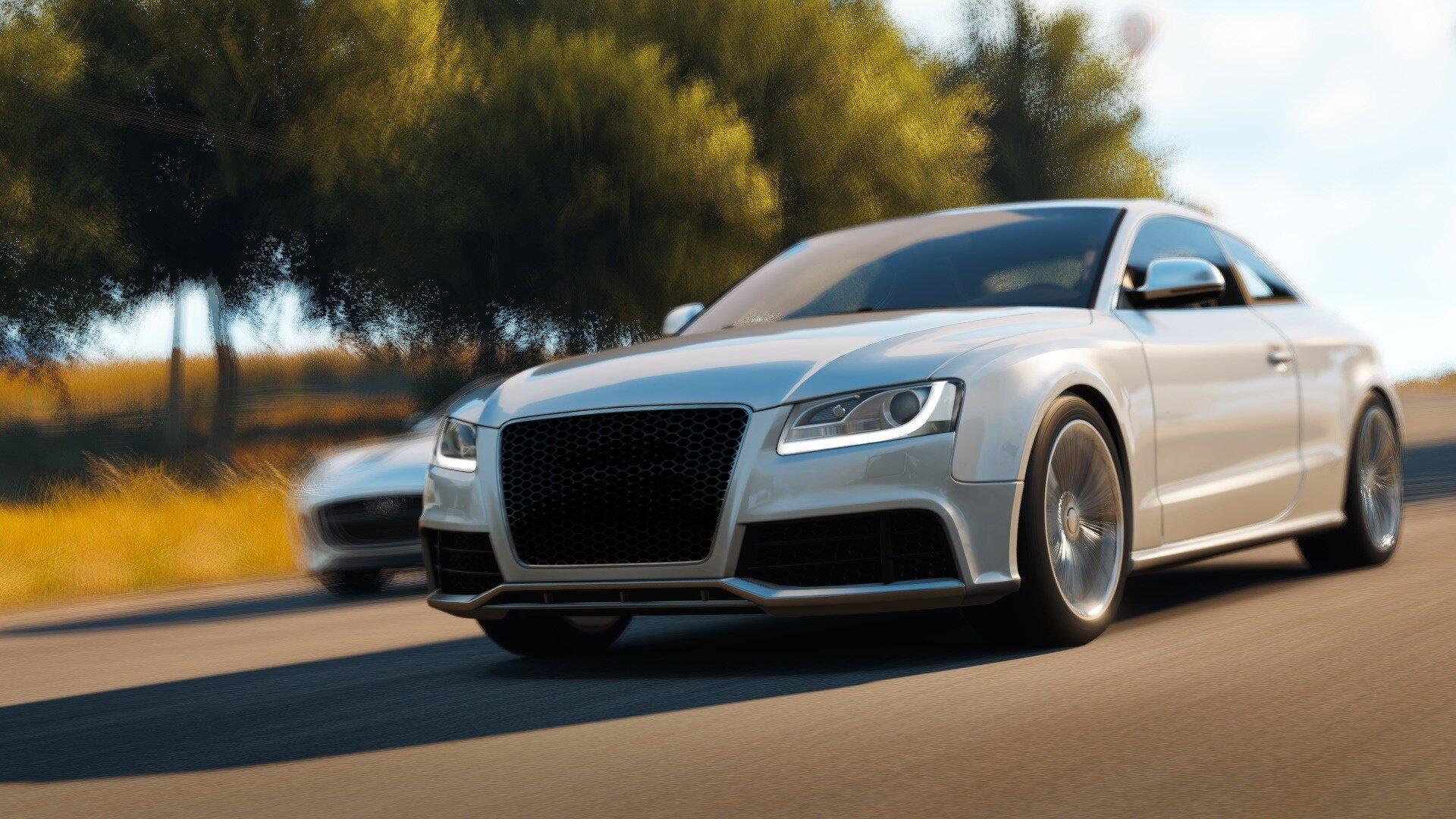 Zdjęcie przedstawia wysokiej klasy samochód wyprzedzający inny na drodze. Na fotografii wyprzedzający znajduje się bliżej aparatu ijest ukazany od dołu. Obraz poprzez zabiegi wizualne, takie jak rozmycie tła ikół auta akcentuje dużą szybkość obu pojazdów.