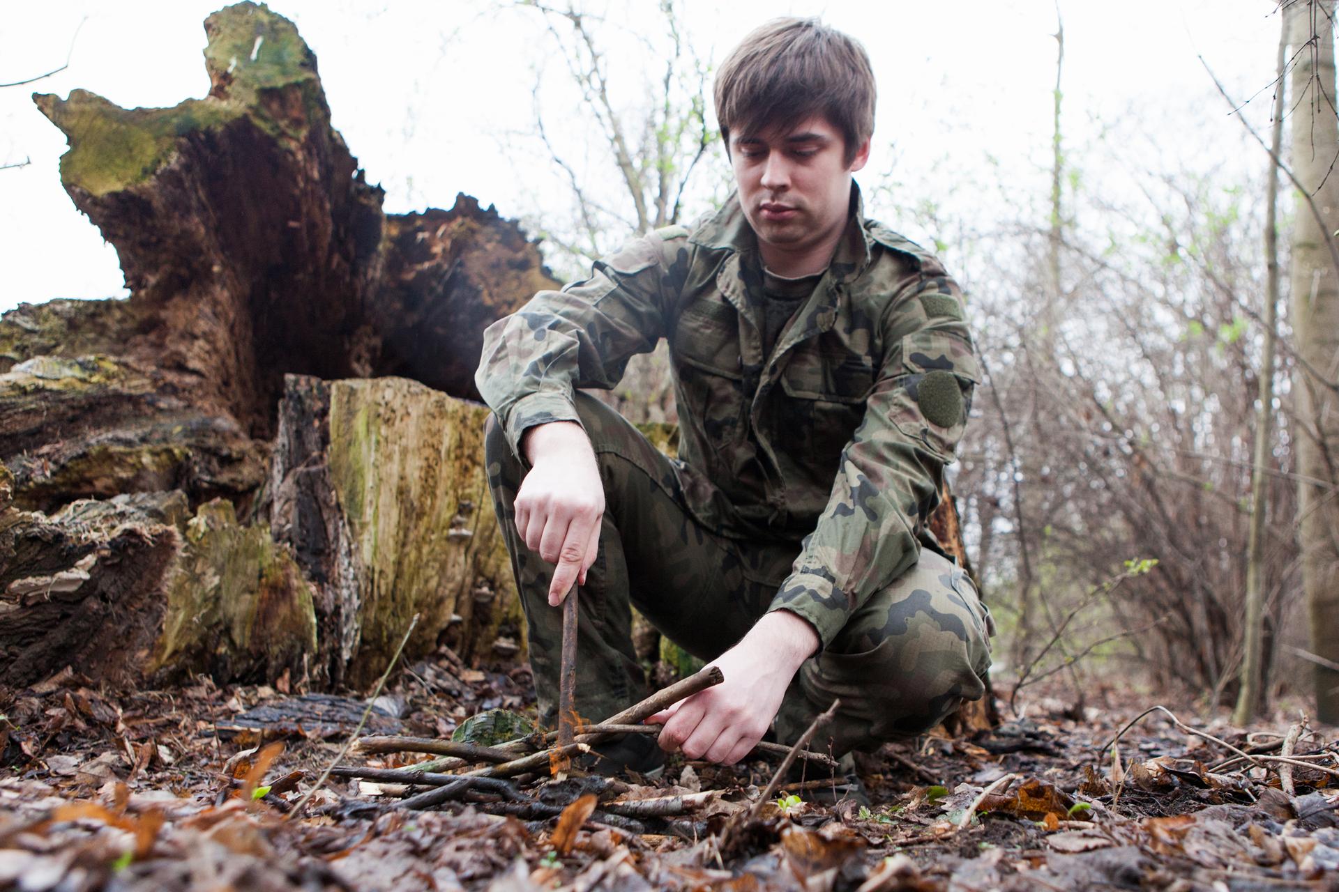 Fotografia przedstawia młodego mężczyznę wprzysiadzie rozpalającego ognisko. Wtle zwalony pień drzewa.