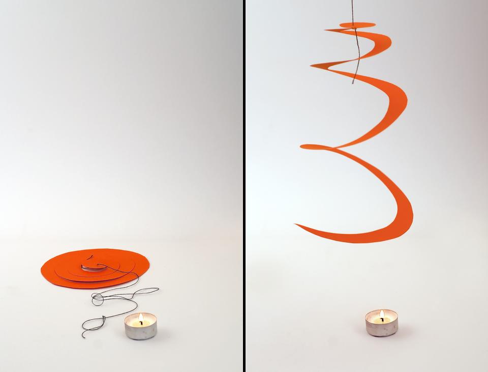Dwie ilustracje przedstawiają sposób unoszenia się nagrzanego powietrza. Do eksperymentu potrzebne są dwie małe świece, zapałki, spiralnie wycięta kartka papieru ośrednicy około 15 centymetrów. Środek spirali jest przyczepiony do sznurka. Na pierwszej ilustracji znajduje się zapalona świeca, które nagrzewa powietrze. Wycięta papierowa spirala leży obok świecy. Na drugiej ilustracji papierowa spirala jest zawieszona nad zapaloną świecą. Spirala jest rozciągnięta na przymocowanym sznurku.