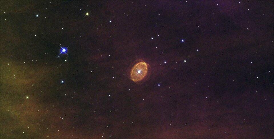 Zdjęcie przedstawia obraz przestrzeni kosmicznej zteleskopu orbitalnego. Centralną część zajmuje bardzo jasna gwiazda otoczona szerokim czerwonym pierścieniem wkształcie elipsy.