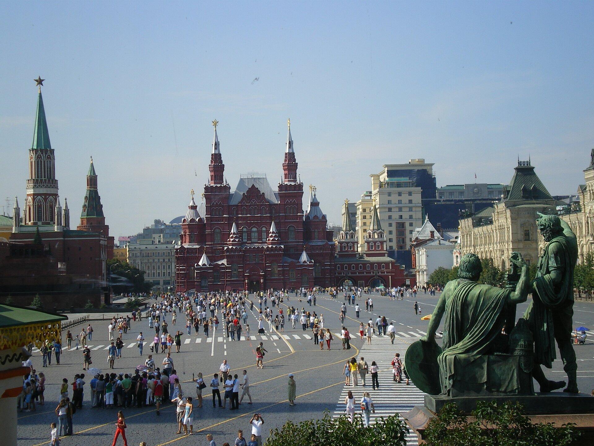 Na zdjęciu kwadratowy asfaltowy plac. Wtle duży czerwony budynek zwieloma wieżami ozdobionymi złotymi gwiazdami. Po lewej iprawej stronie okazałe budynki. Na pierwszym planie po prawej stronie rzeźba wkolorze zielonym, dwóch mężczyzn, jeden siedzi, drugi stoi. Na całym placu jest wielu ludzi, stoją wgrupach, idą, na ulicy namalowane żółte linie, przejścia dla pieszych.