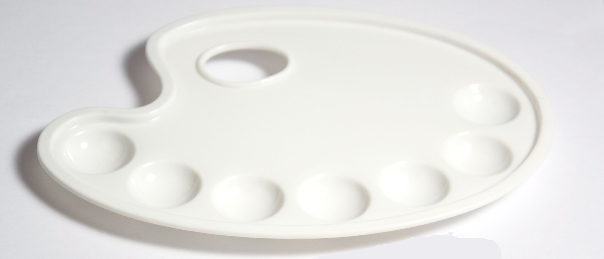 Ilustracja przedstawia białą, plastikową paletę zotworem na kciuk, który pomaga wtrzymaniu jej podczas pracy. Na powierzchni palety znajdują się wgłębienia ułatwiające mieszanie kolorów. Przedmiot umieszczony jest na białym tle.