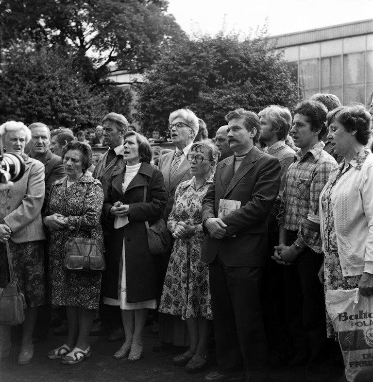 na zdjeciu grupa ludzi podczas mszy świętej na strajku wstoczni gdańskiej w1980 r., wśrod nich Anna Walentynowicz iLech Wałęsa