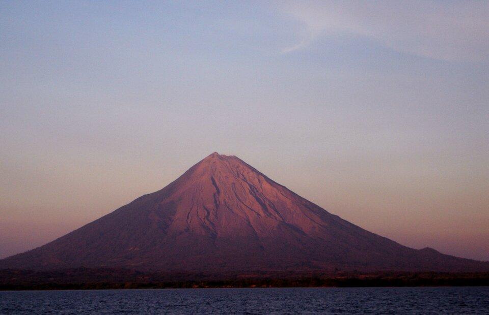 Fotografia prezentuje wysoki stożek wulkaniczny położony nad wodą.