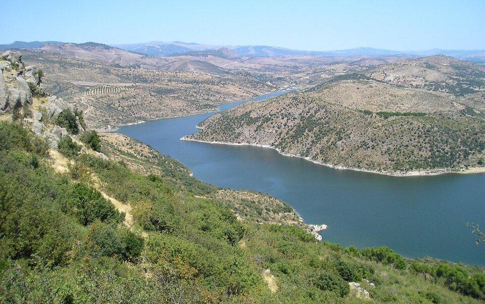 Na zdjęciu pofałdowane tereny porośnięte suchą roślinnością makii. Wśrodku zbiornik wodny.