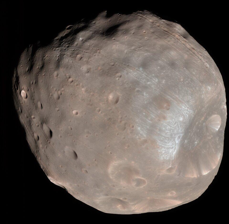 Zdjęcie przedstawia jeden zdwóch księżyców Marsa – Fobos. Tło czarne. Kształt księżyca zbliżony do kuli, powierzchnia nieregularna. Widoczne małe, okrągłe zagłębienia – kratery. Kolor szarobrązowy, matowy.