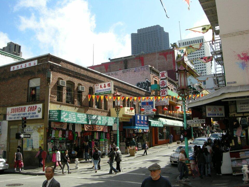 Na zdjęciu gęsto zabudowana ulica wmieście, liczne reklamy iszyldy znapisami wjęzyku chińskim.