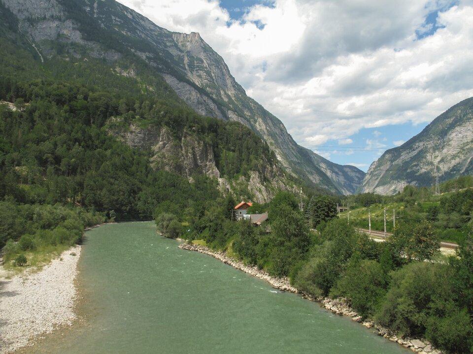 Na zdjęciu głęboka dolina rzeki. Wzdłuż rzeki linia kolejowa, zabudowania. Dookoła strome stoki porośnięte gdzieniegdzie roślinnością.