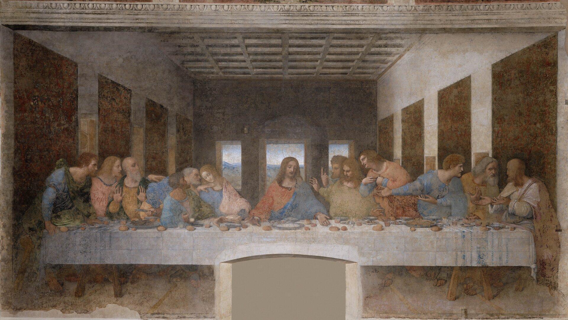 """Ilustracja przedstawia malowidło Leonarda da Vinci """"Ostatnia wieczerza"""". Scena przedstawia Jezusa idwunastu apostołów, znajdujących się za stołem, przykrytym białym obrusem, na którym leżą małe bochenki chleba oraz naczynia. Jezus siedzi pośrodku, ubrany jest wczerwoną ibłękitną szatę. Dłonie ma położone na stół. Apostołowie pogrupowani są po trzy osoby. Prowadzą między sobą rozmowę, gestykulując. Wścianach bocznych wnętrza znajdują się wnęki, awścianie ztyłu trzy podłużne okna. Sufit zdobiony jest kasetonami."""