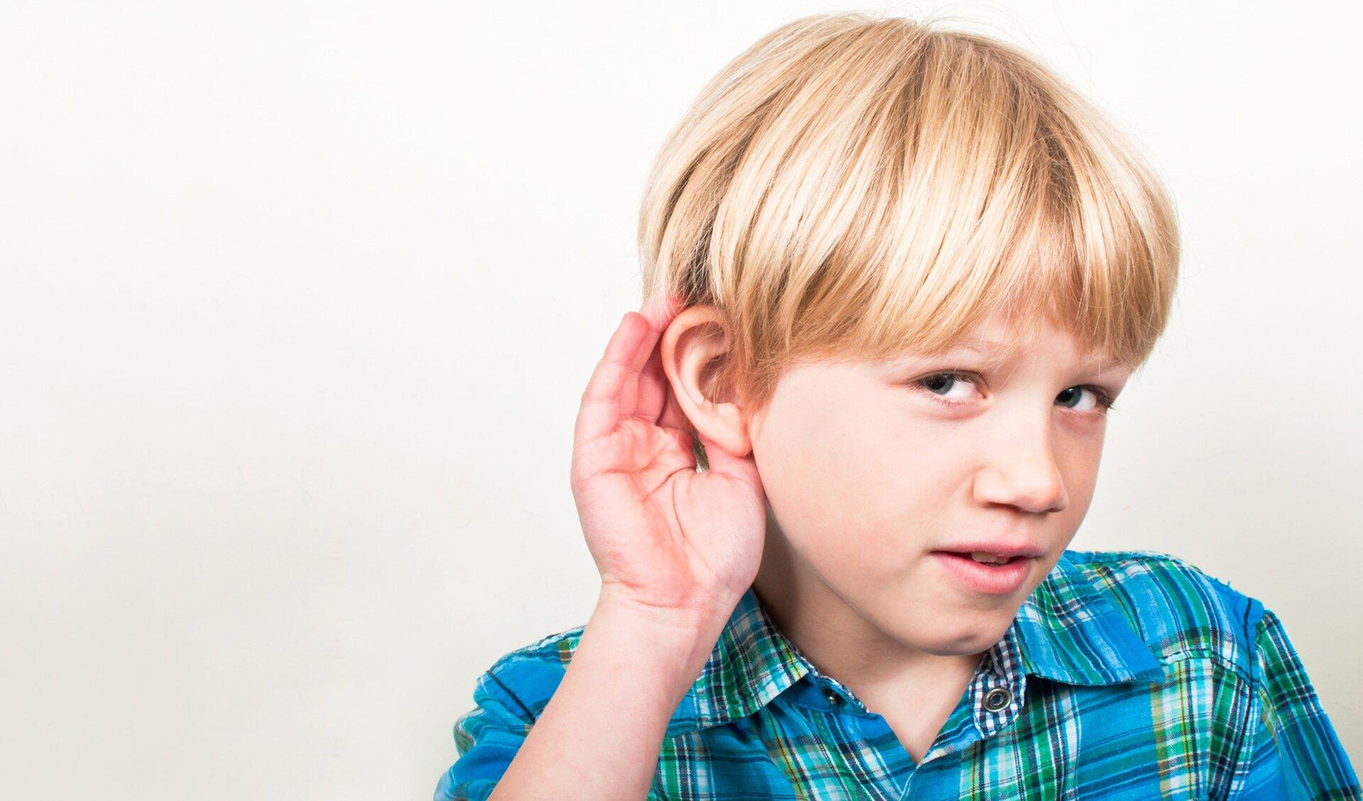 Fotografia przedstawia nasłuchującego chłopca
