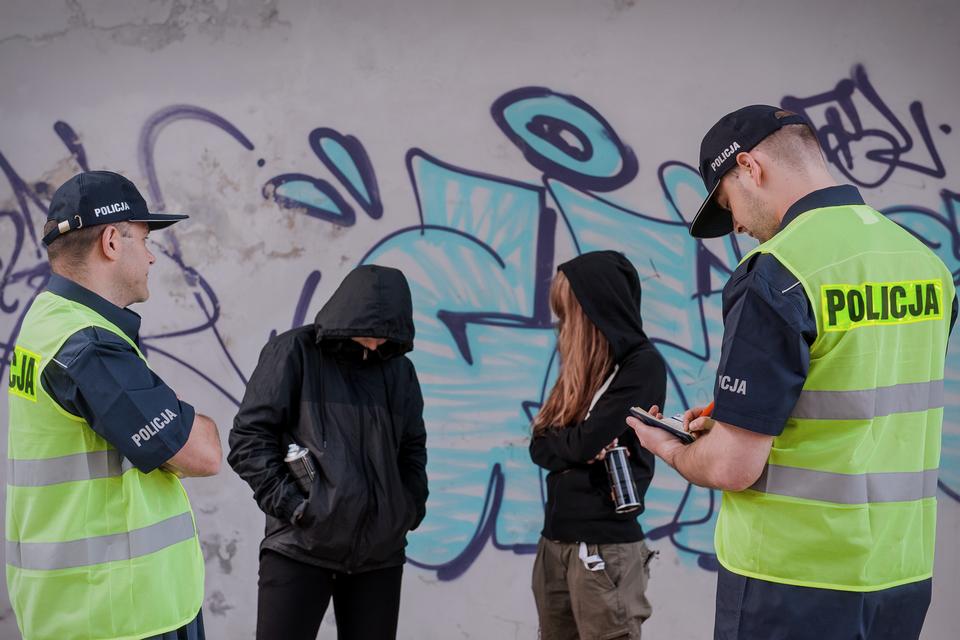 Zdjęcie przedstawiające policjantów wlekkich letnich mundurach ikamizelkach odblaskowych znapisami Policja wypisujących dwójce młodych ludzi mandaty za wandalizm. Policjanci stoją tyłem do obserwatora zdjęcia. Przed nimi dwoje młodych ludzi wkapturach na głowie ze sprejami wrękach. Za nimi na murze widoczne graffiti.