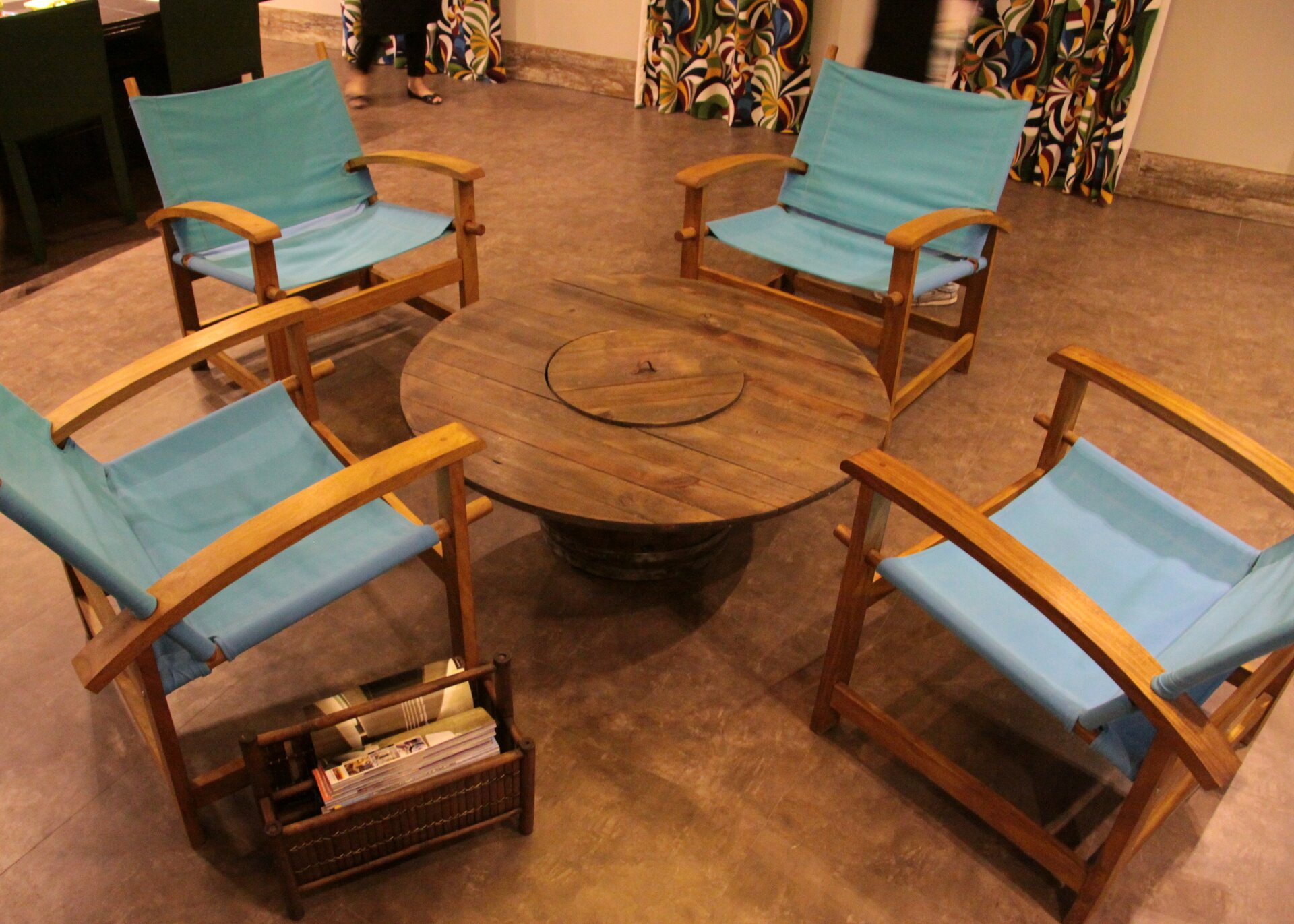 Na zdjęciu szpula do kabli energetycznych wykorzystana jako stół. Dookoła szpuli cztery zielone fotele.